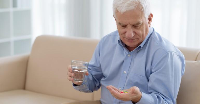 Man Looking at Pills