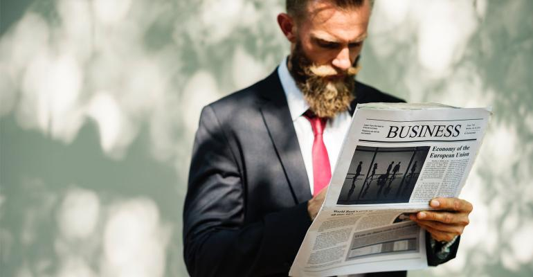 Busines Man Reading Business Section of Newspaper