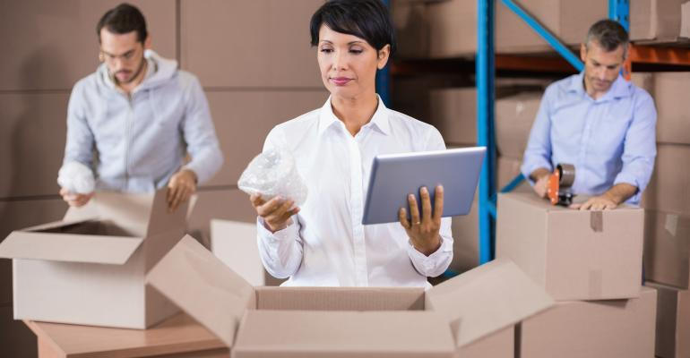People in Warehouse Packing Cardboard Boxes