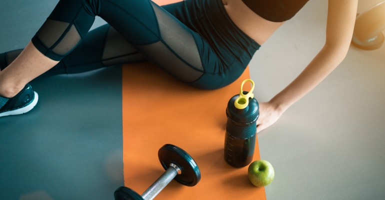 Exercising Woman Sitting Next To Bottle