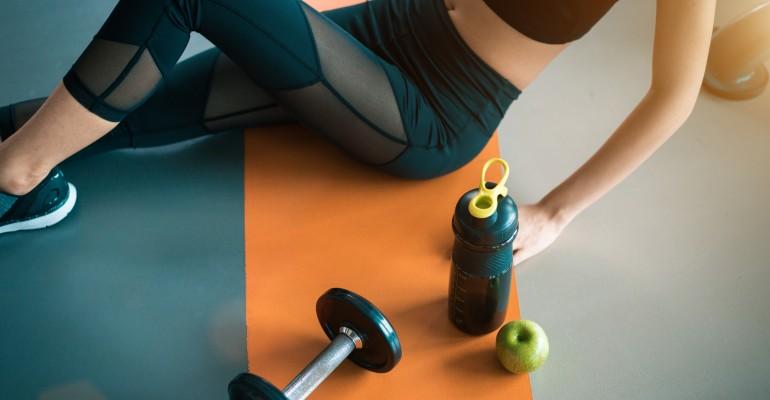 Exercising Woman Sitting Next To Bottle