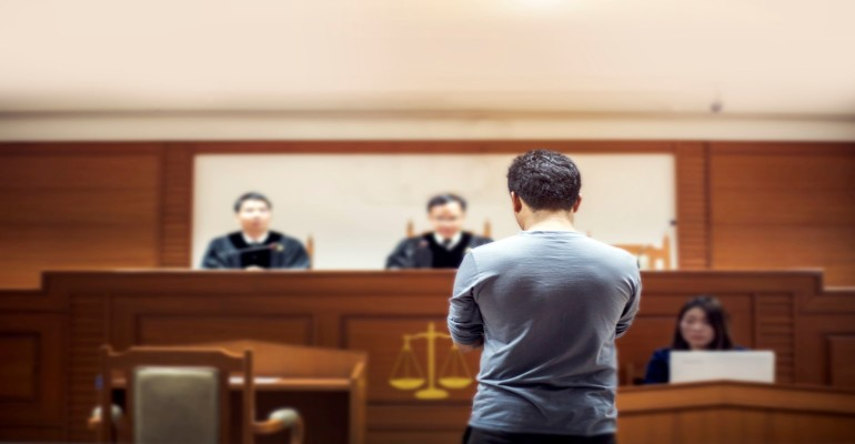 man standing in front of two judges in court