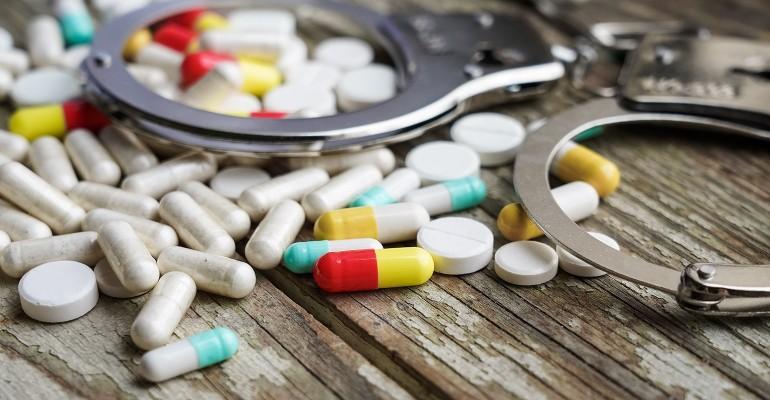 handcuffs and pills on wood RETINA.jpg