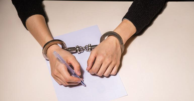 detainee signing plea while handcuffed